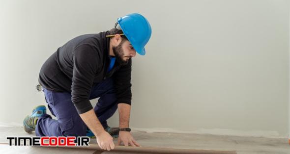Man Carpenter Assembling Laminate Flooring. House Floor Renovation